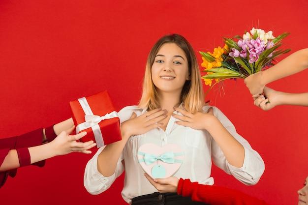 Alle cadeaus en bloemen. valentijnsdagviering. gelukkig, leuk kaukasisch meisje dat op rode studioachtergrond wordt geïsoleerd. concept van menselijke emoties, gezichtsuitdrukking, liefde, relaties, romantische vakanties.