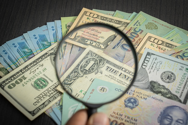 Alle geldstapels us dollar usd, vnd, dong pay, wissel vietnamees en vergrootglas op cijfers