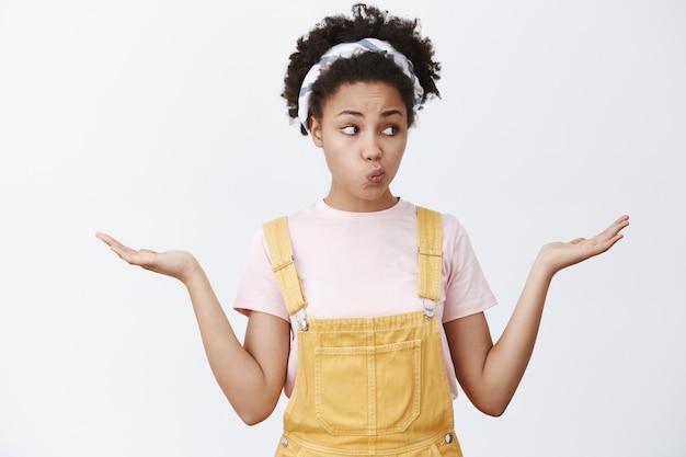 Alle keuzes afwegen, onzeker voelen wat voor keuze. portret van charmante afro-amerikaanse vrouw met producten in handen, starend met gevouwen lippen rechts terwijl het nemen van een beslissing over grijze muur