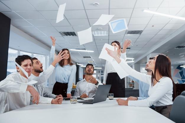 Alle papieren hangen in de lucht. de klus is geklaard. groep van kantoorpersoneel blij om hun eigen records te slaan en succesvol te zijn