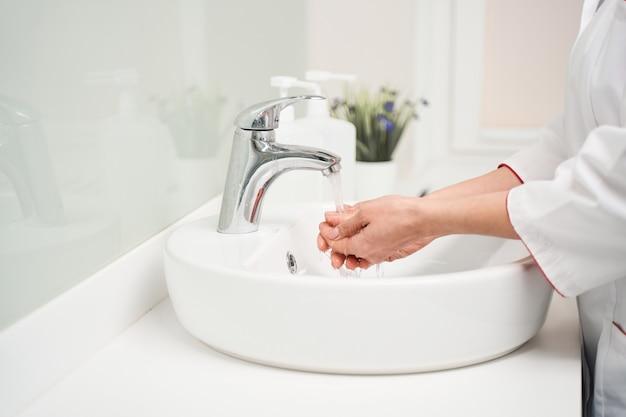 Alledaags ritueel. jonge beoefenaar die medisch uniform draagt en haar handen wast voor de werkdag