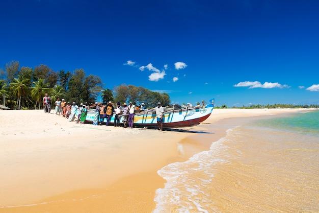 Alledaagse vissers laten de boot in het water zakken en sturen hem na het vissen terug naar het zandstrand, kalkuda sri lanka.