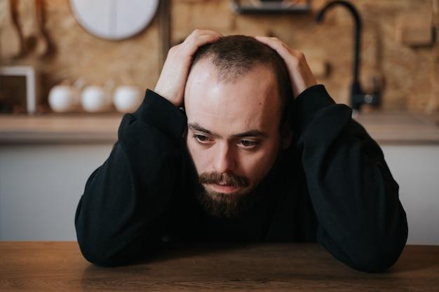 Alleen bebaarde man, verdrietig in depressie, op de tafel in de keuken, in huis, binnenshuis