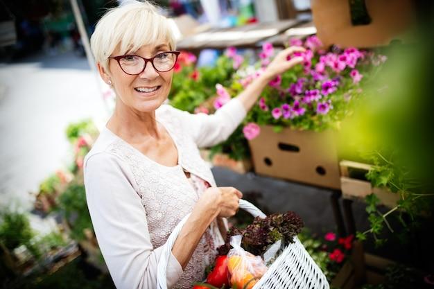 Alleen de beste groenten en fruit. mooie rijpe vrouw die vers voedsel op markt koopt