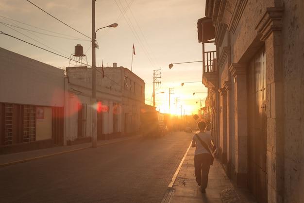 Alleen de stad in lopen bij zonsondergang in tegenlicht