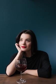 Alleen dromend jong wijfje in bar. toekomstperspectieven in het leven, melancholische stemming met rode wijn op blauwe achtergrond met vrije ruimte, droomconcept