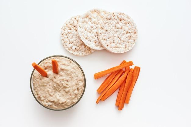 Alleen een nuttig tussendoortje. hummus met worteltjes. bovenaanzicht van humus met broden evenwicht geïsoleerd op een witte achtergrond.