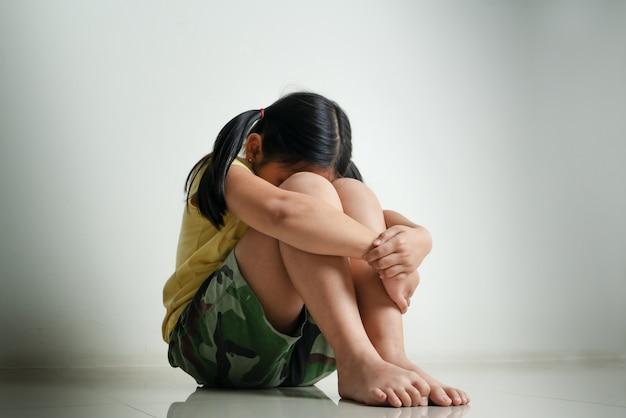 Alleen en bang, droevige depressieve kinderen huilen in de donkere kamer nadat ze gepest zijn