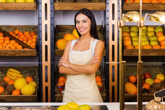 Alleen het meest verse fruit in onze winkel. mooie jonge vrouw in schort die de armen gekruist houdt en glimlacht terwijl ze in de supermarkt staat met verschillende soorten fruit op de achtergrond