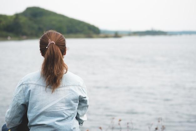 Alleen hipster vrouw zittend op de oever van het meer op zoek buiten water en berg achtergrond.