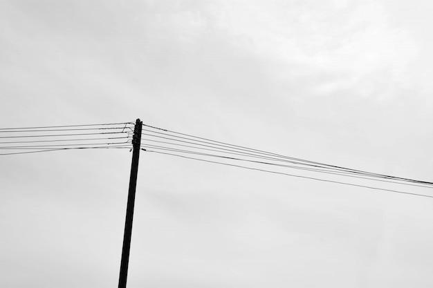 Alleen houten pyloon met draden in landelijk - zwart-wit
