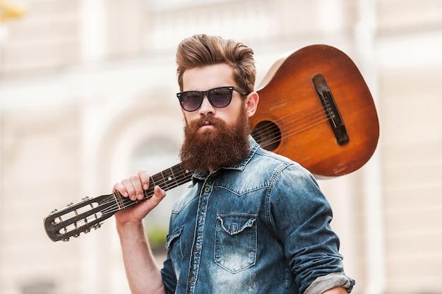 Alleen ik en mijn gitaar. lage hoekmening van jonge, bebaarde man die zijn gitaar op zijn schouder draagt en naar de camera kijkt terwijl hij buiten staat