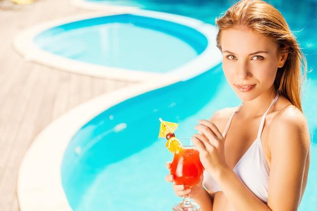 Alleen ik en mijn zomercocktail. mooie jonge vrouw in witte bikini die een cocktail vasthoudt en naar de camera kijkt terwijl ze aan het zwembad ontspant