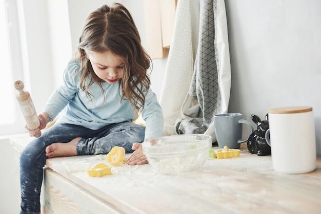 Alleen in de kamer als ouders niet thuis zijn. foto van mooi meisje dat op de keukentafel zit en met bloem speelt