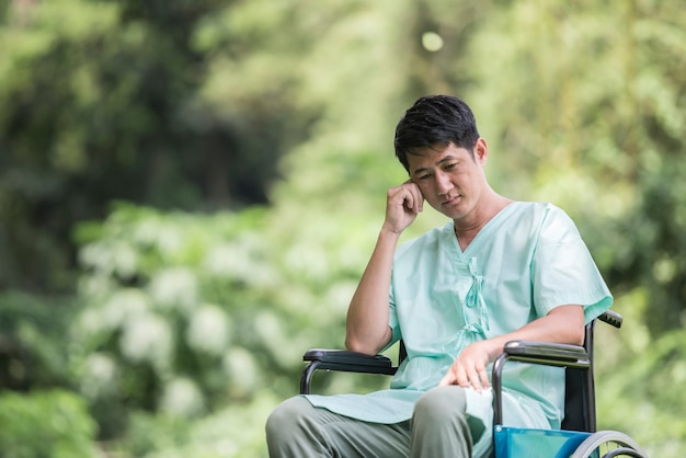 Alleen jonge gehandicapte man in rolstoel in de tuin