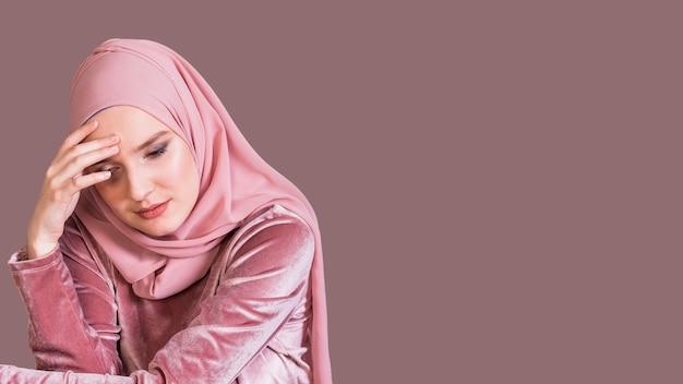Alleen jonge moslimvrouw die neer over gekleurde achtergrond kijkt