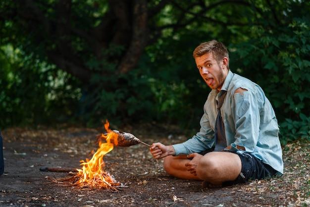 Alleen kantoormedewerker warmt op bij het vuur op onbewoond eiland.
