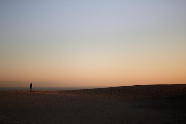 Alleen man op het strand met silhouet van een duin
