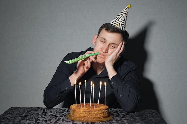 Alleen man viert een vakantie, hij zit alleen aan een tafel met een taart en een kaars.