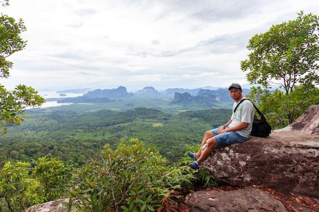 Alleen man zittend op de rand van de klif en op zoek naar landschap bekijken regenwoud dragon crest gelegen op khao ngon nak in krabi thailand.