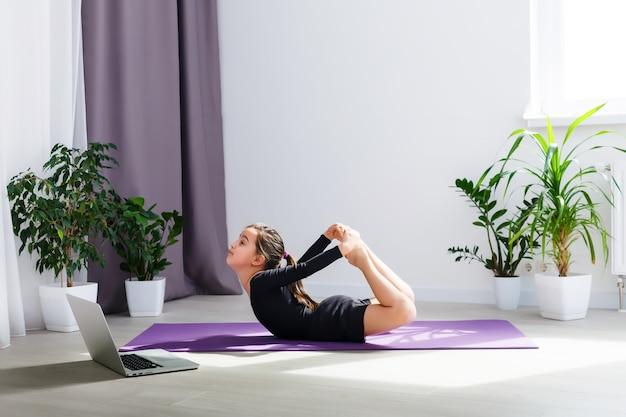Alleen meisje doet yoga-oefeningen online op laptop op de vloer in de lichte kamer, blijf thuis veilige wereld.