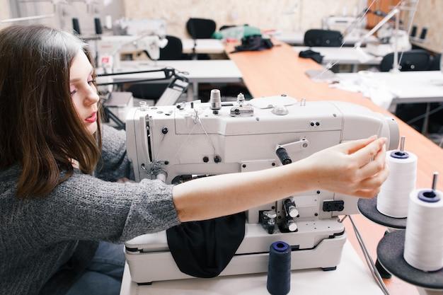 Alleen naaister die overwerkt in de kledingfabriek.