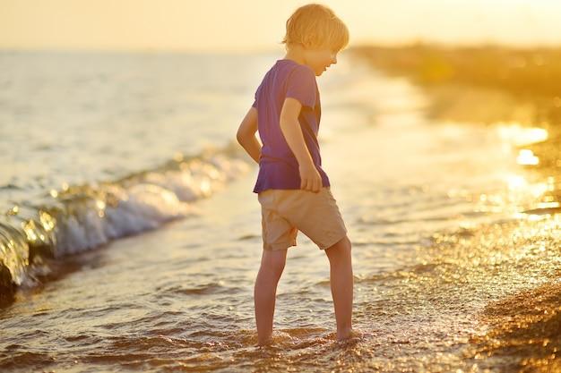 Alleen peuterjongen die tijdens vakantie blootsvoets langs de kust loopt