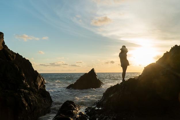 Alleen reismeisje op strandzonsondergang