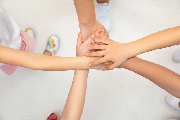Alleen samen zijn we sterk. de handen van kinderen zijn samengevoegd op de witte vloerwand