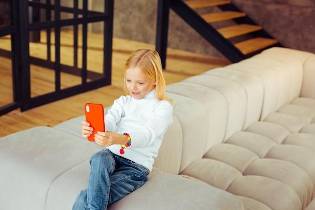 Alleen thuis. charmante jongen zittend op de bank en kijkend naar het scherm van haar gadget