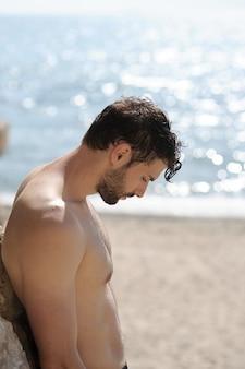 Alleen trieste man profiel portret op een strand, topless buitenfoto