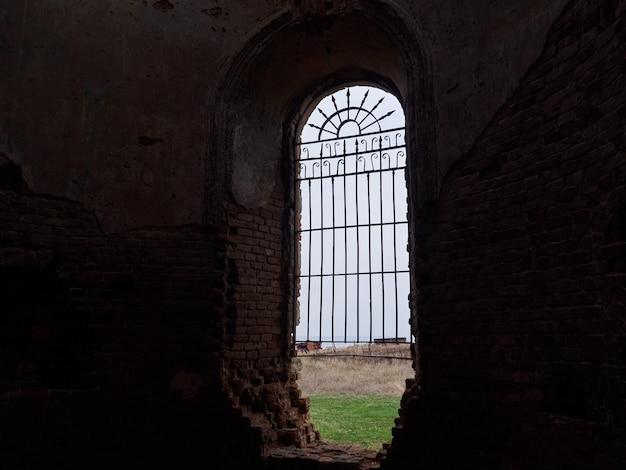 Alleen venster met tralies in een donker oud gebouw met uitzicht op het veld