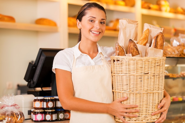 Alleen vers brood voor onze klanten. mooie jonge vrouw in schort die mand met brood vasthoudt en glimlacht terwijl ze in de bakkerij staat