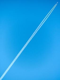 Alleen vliegtuig in blauwe paarse hemel trace witte diagonale lijn