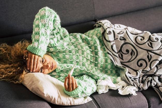Alleen vrouw thuis liggend op de bank kijkend naar de thermometer met hoge koorts