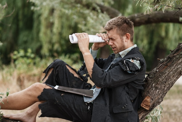 Alleen zakenman in gescheurd pak die op de boom op het verloren eiland rust.