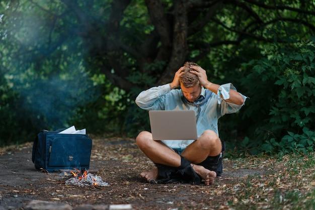 Alleen zakenman met laptop bij de open haard op onbewoond eiland.