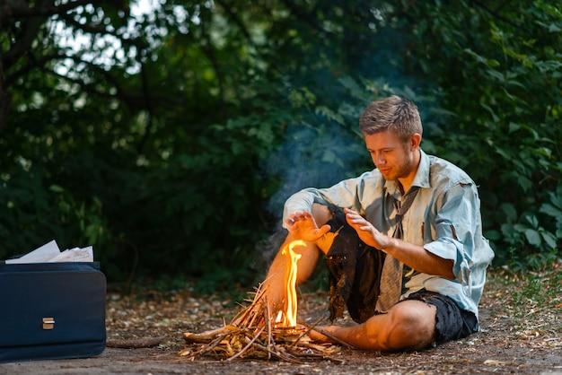 Alleen zakenman warmt op bij het vuur op het verloren eiland.