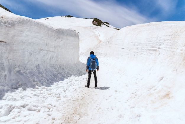 Alleenstaande man staande op sneeuw loopbrug op tateyama kurobe alpine route.