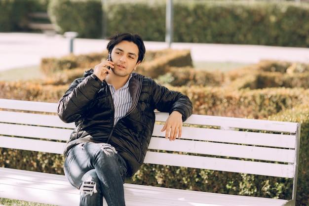 Alleenstaande man zittend op de bank in het park en praten met de telefoon. hoge kwaliteit foto