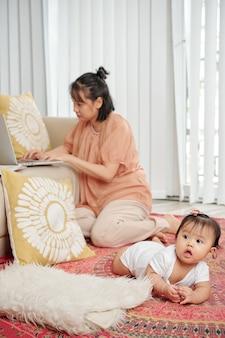 Alleenstaande moeder die op laptop werkt