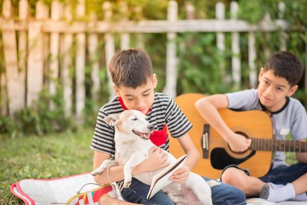 Alleenstaande moeder en zonen spelen guitartogether met plezier in het park
