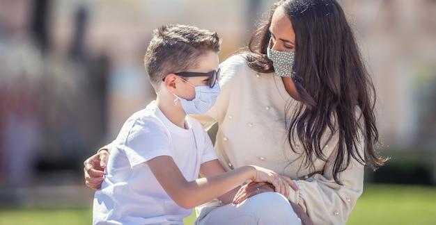 Alleenstaande moeder kijkt bezorgd naar haar zoon in zonnebril buiten, beide met gezichtsmaskers.