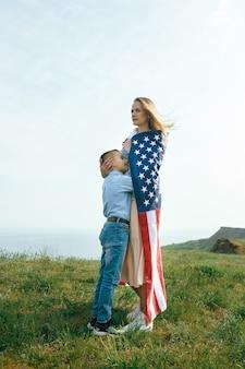Alleenstaande moeder met zoon op onafhankelijkheidsdag van de vs vrouw en haar kind lopen met de vlag van de verenigde staten aan de oceaan kust