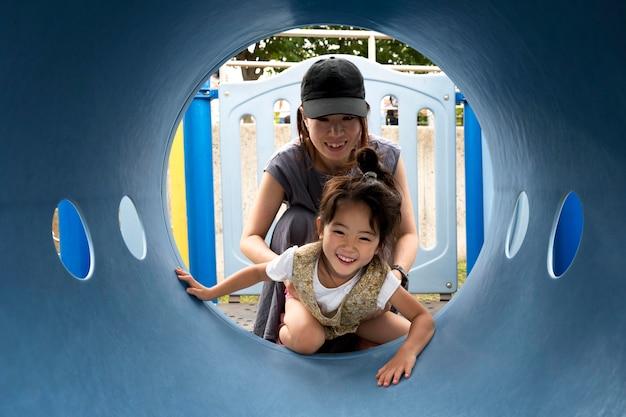 Alleenstaande moeder speelt met haar dochter in een park