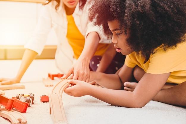Alleenstaande moeder woont met twee dochters die puzzelspeelgoed leren en spelen in een appartement thuis. nanny kijken of kinderopvang bij woonkamer zwarte mensen.