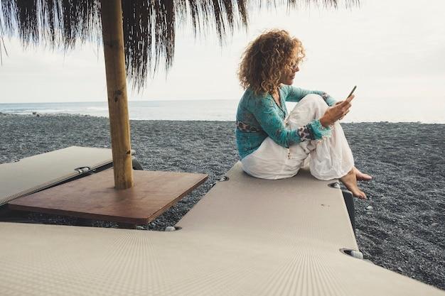Alleenstaande mooie blanke vrouw van middelbare leeftijd op het strand gaat op de stoelen zitten met de oceaan en het zand om haar heen en controleert de telefoon om internet en e-mails te zien en te werken buiten het kantoor, blijf verbonden