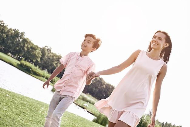 Alleenstaande ouder moeder en zoon lopen op een grasveld in de buurt van lak