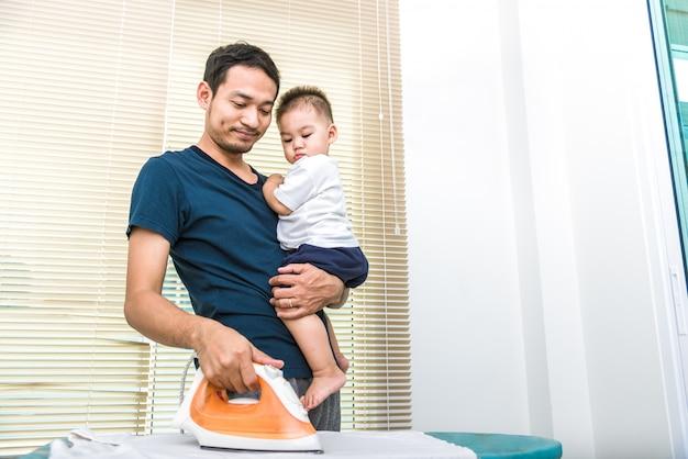 Alleenstaande vader strijkt terwijl hij zijn zoon draagt. mensen en leefstijlen concept.