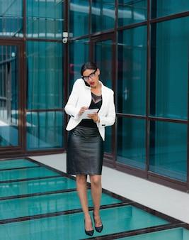 Allemaal aan het werk. jonge afro zakenvrouw praten aan de telefoon en belangrijke informatie in notitieblok schrijven